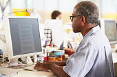 Man Working At Desk In Busy Creative Office Concentrating