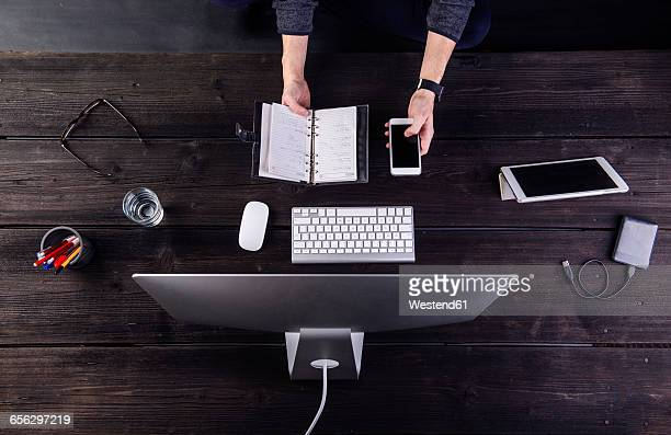 Man working at desk with computer and various digital gadgets, updating personal organizer