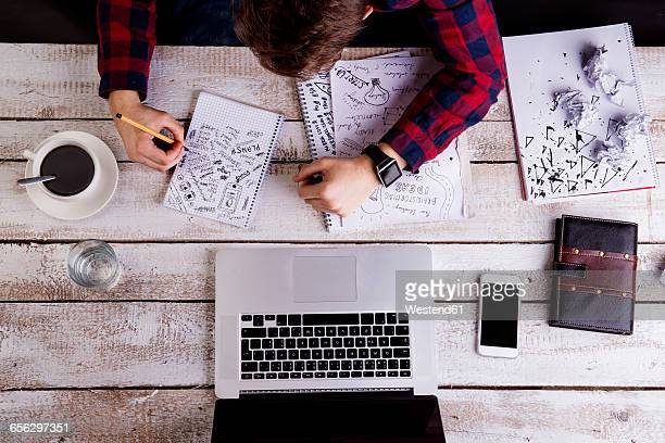 Man working at desk with laptop, making notes