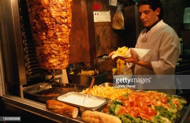 Man working at doner kebab stand.