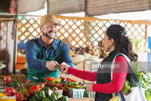 Man working at farmer's market taking cash from customer