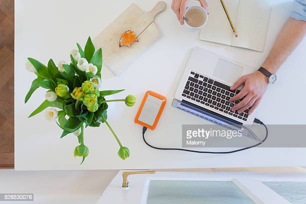 Man working at home office with laptop while drinking coffee