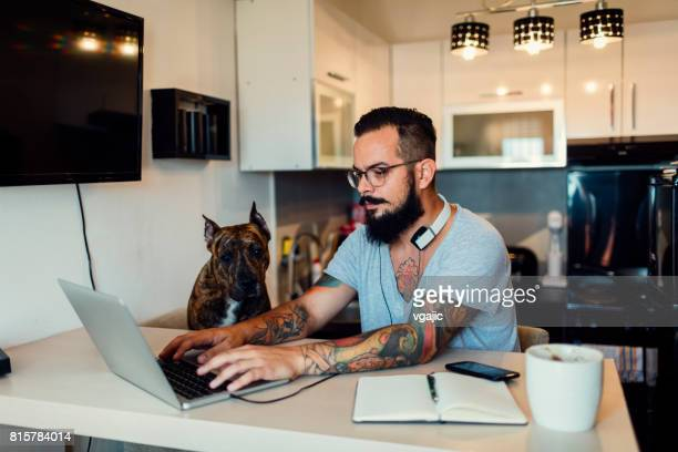 Man working at home with his dog next to him