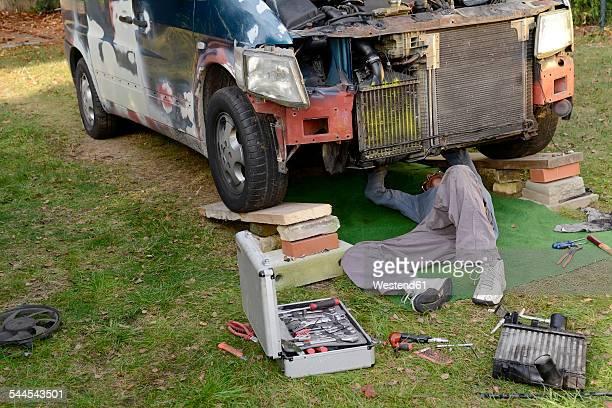 Man working at old van outdoors