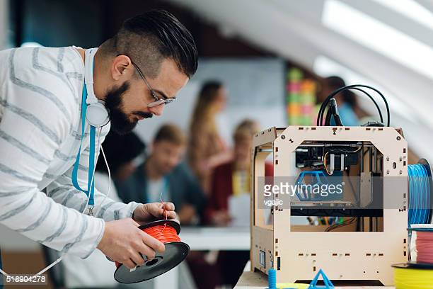 Man Working by 3D Printer in start-up Business office.