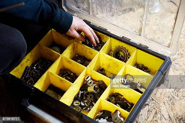 A man working in a cycle shop, reaching for parts in a box of spares.