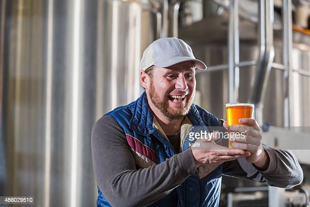 Man working in a small brewery holding beer