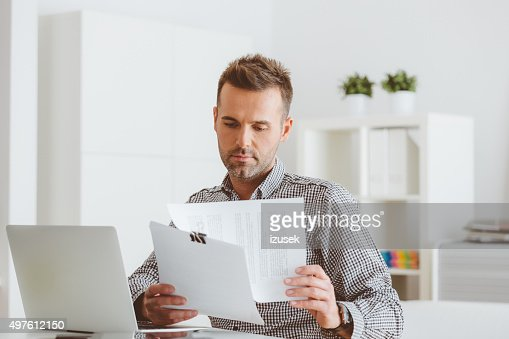 Man working in an home office, reading documents