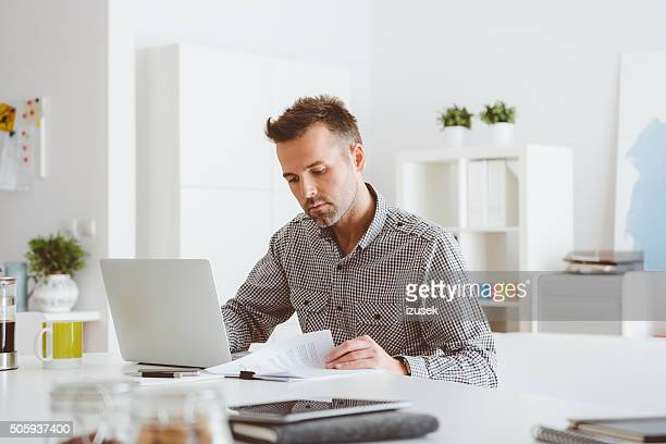 Man working in an home office, using computer, reading documents