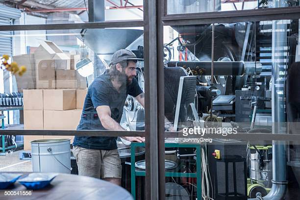 Man working in coffee roasting warehouse, using computer with machinery