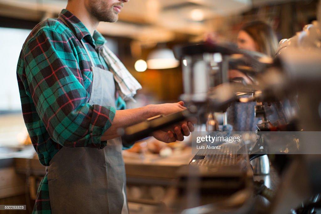 Man working in coffee shop : Stock Photo