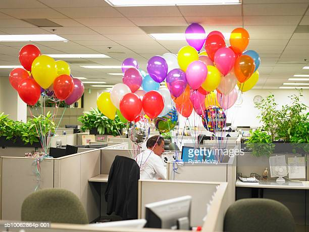 Man working in cubicle surround by balloons