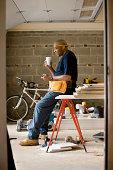 Man working in garage taking coffee break