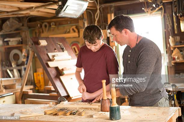 Man working in his workshop helping kid use chisel