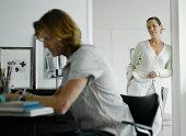 Man working in home office, woman standing in door