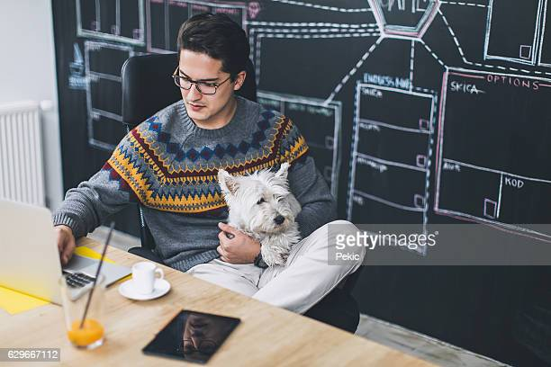 Man working in office and holding his cute dog