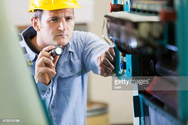 Man working in printing plant inspecting machine