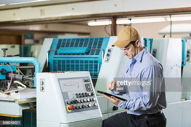 Man working in printshop by machine with digital tablet