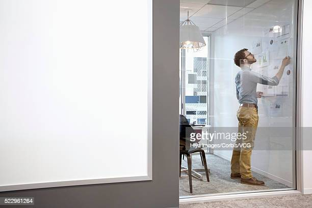 Man working in room behind glass wall, whiteboard in foreground