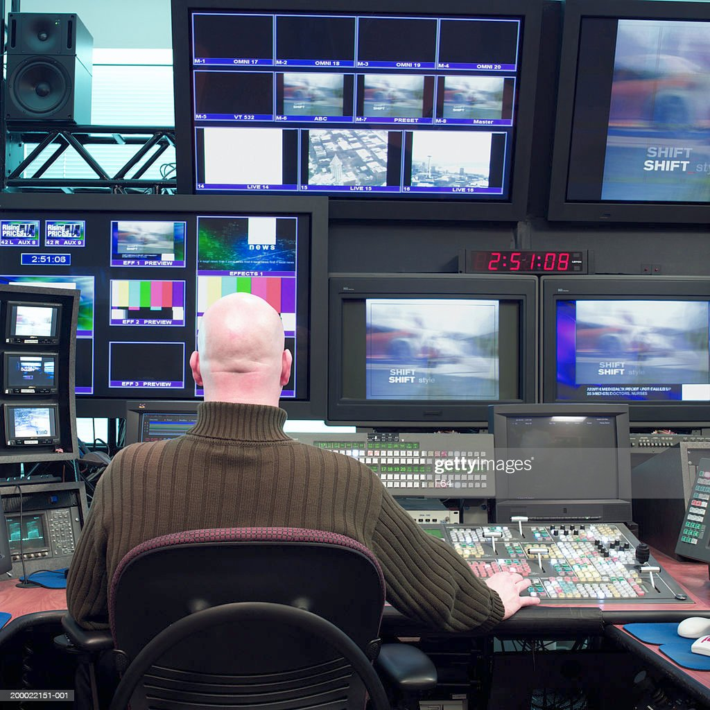 Man working in television studio control room, rear view