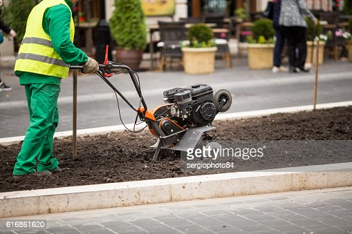 Man working in the city streets with Garden Tiller. Close : Stock Photo