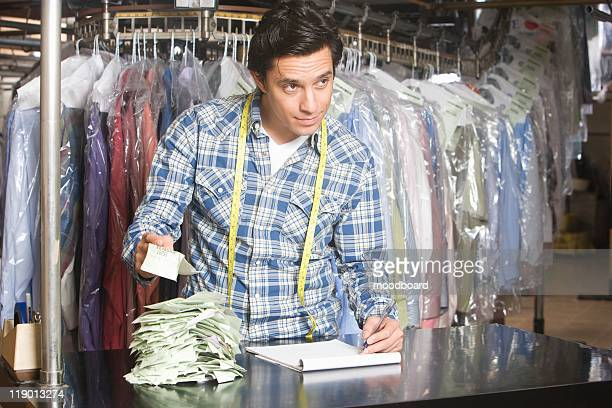 Man working in the laundrette documenting receipts
