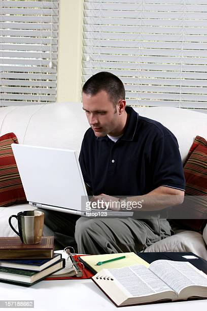 Man working. Laptop computer at home.  Books on coffee table.