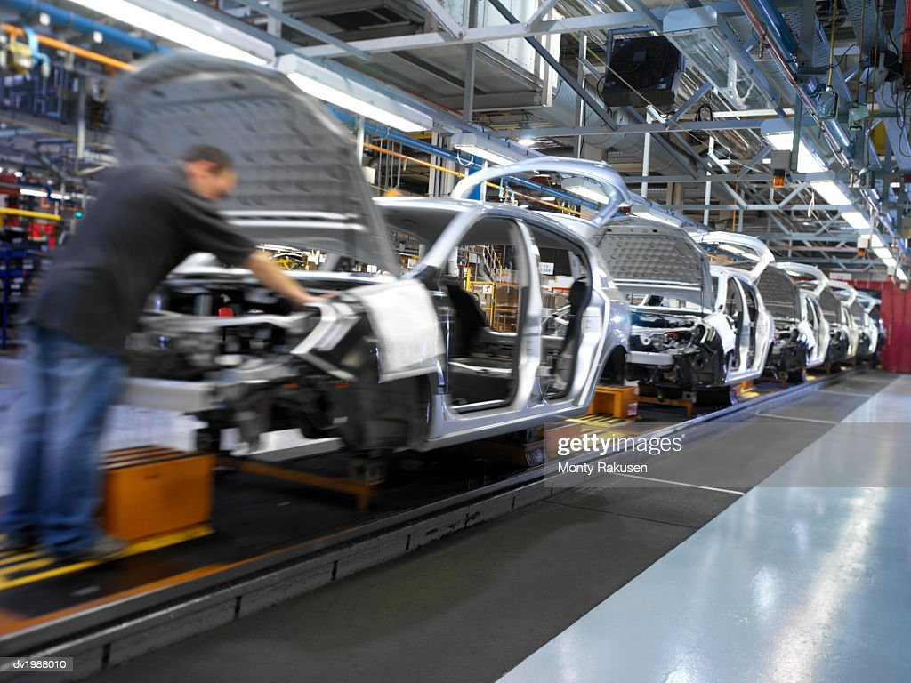 Man Working on a Car Assembly Line in a Factory : Stock Photo