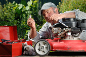 Man working on a lawnmower in the garden.