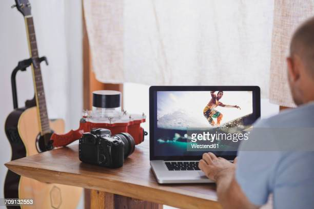 Man working on a photography on laptop display