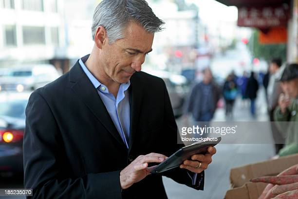 Man working on a tablet in the city on the go