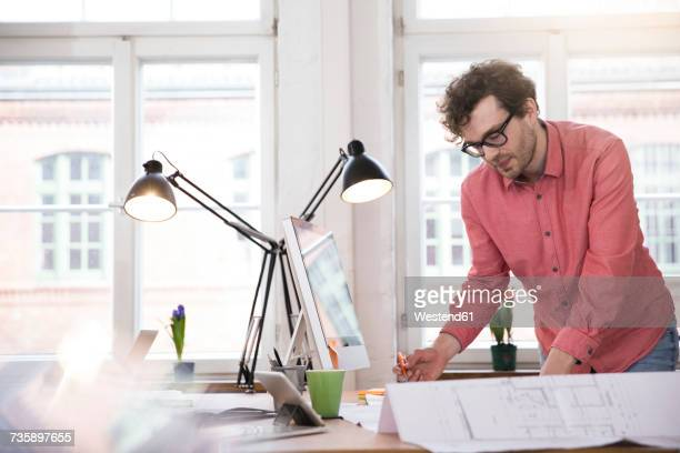Man working on blueprint at desk in office