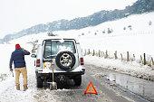 Man working on broken down car in snow