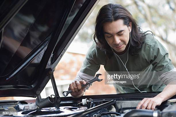 Man working on car and listening to headphones