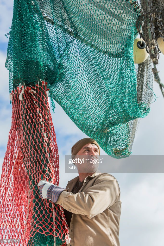 Man working on commercial fishing boat, preparing net : Stock Photo