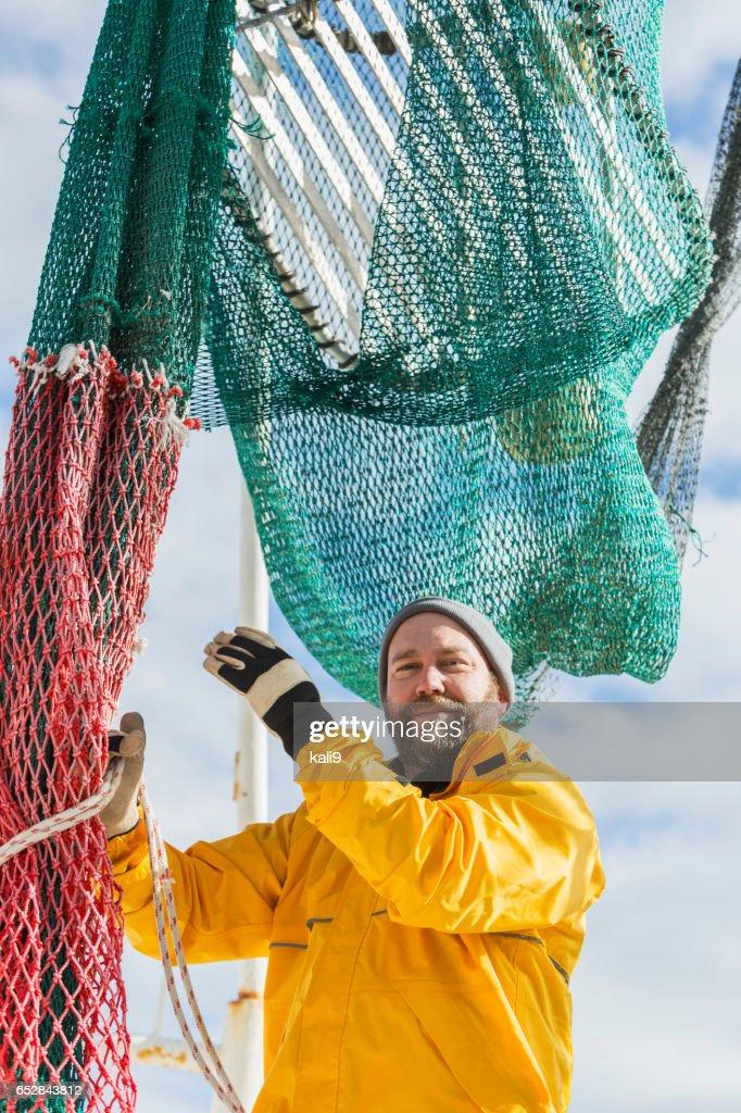 Man aan het werk op commerciële vissersboot, net voorbereiding : Stockfoto