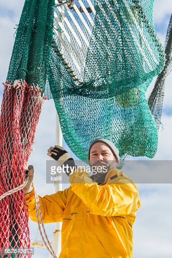 Man working on commercial fishing boat, preparing net : Stockfoto