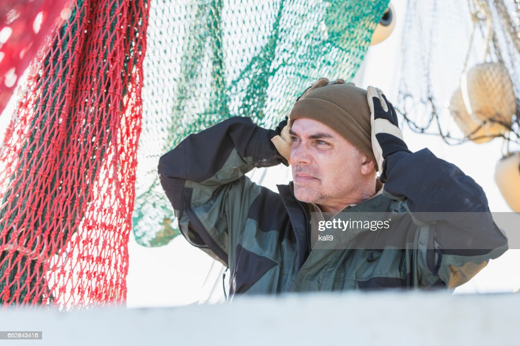 Man working on commercial fishing boat putting on hat : Stockfoto