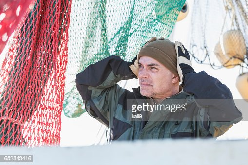 Man working on commercial fishing boat putting on hat : Bildbanksbilder