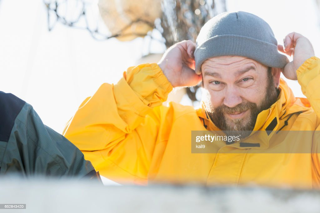 Man working on commercial fishing boat putting on hat : Stock-Foto