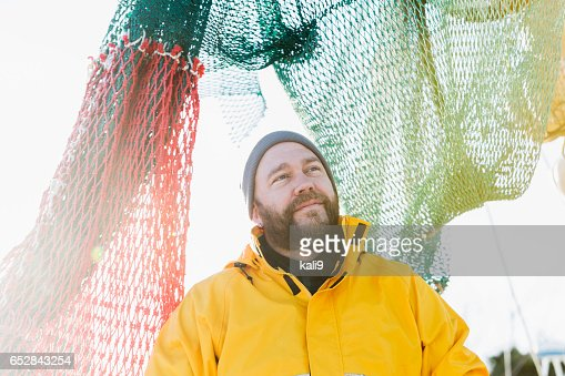 Man working on commercial fishing vessel : Stock-Foto