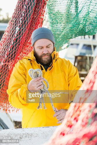 Man working on commercial fishing vessel : Foto stock