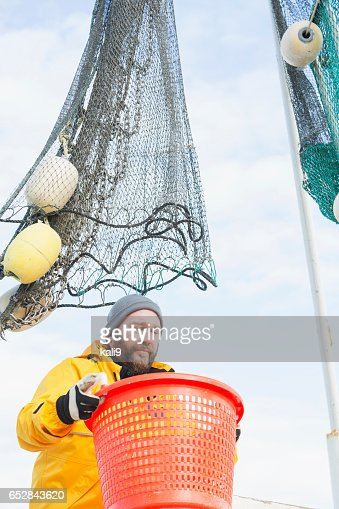 Man working on commercial shrimp boat carrying basket : ストックフォト