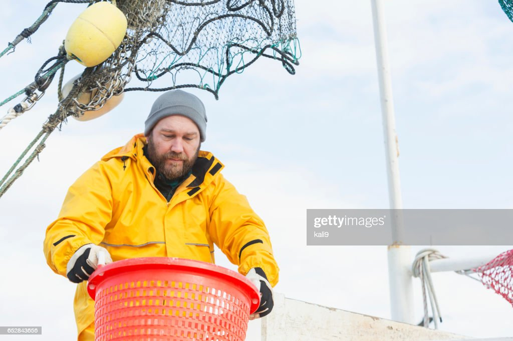 Man working on commercial shrimp boat carrying basket : Stock Photo
