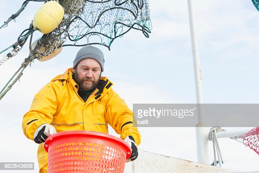 Man working on commercial shrimp boat carrying basket : Stock-Foto