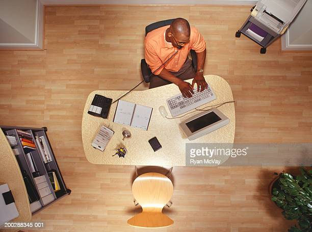 Man working on computer in office, talking on phone overhead view