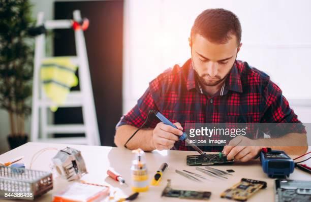 Homme travaillant sur la carte mère d'ordinateur portable de fixation