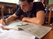 Man Working on His US Taxes with 1040 Tax Instruction Book and Calculator on Table