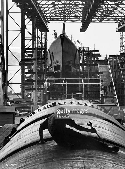 Man working on hull of a US submarine at the Electric Boat Company Groton Connecticut August 1943 | Location Electric Boat Company Groton Connecticut...