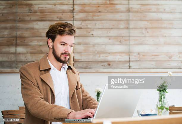 Mann arbeitet auf dem laptop im Café